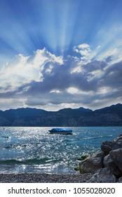 beautiful garda lake with little boat. dramatic cloud with sunbeams, italy