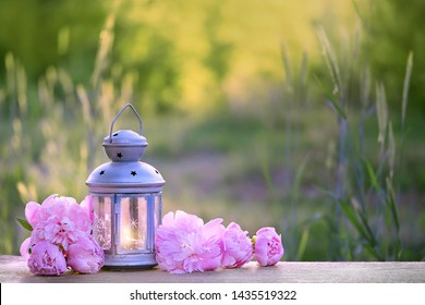beautiful garden decor with pink summer flowers and lantern. Flower peony with garden lantern in spring or summer meadow. Garden party decorations. summer season. banner. copy space.