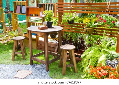 beautiful garden with flower and wooden table and chairs - home decoration