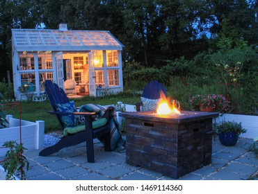 Beautiful Garden Scene at Dusk with Firepit, Andirondack Chairs and Greenhouse with lit chandelier