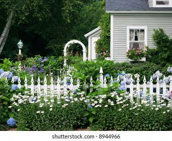 beautiful garden setting with flowers and white picket fence