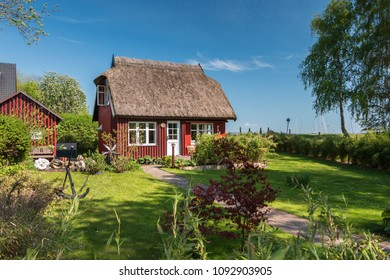 Beautiful garden of a typical village house with thatched roof at the Baltic Sea