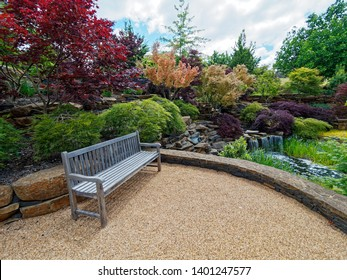 Beautiful garden with  vibrant colours of Autumn trees and bench seat,  Oberon,  New South Wales,  Australia.