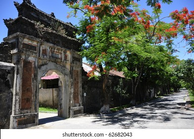 Beautiful gate close to a tree with red flowers at the Hue Citadel, Vietnam