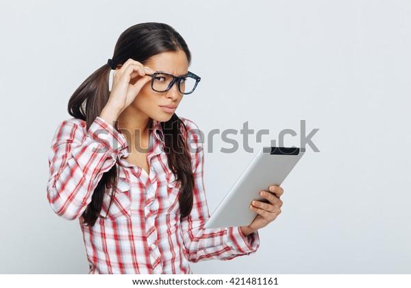 Beautiful geek woman holding digital tablet in studio on white