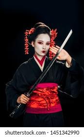 beautiful geisha in black kimono with flowers in hair holding katana isolated on black