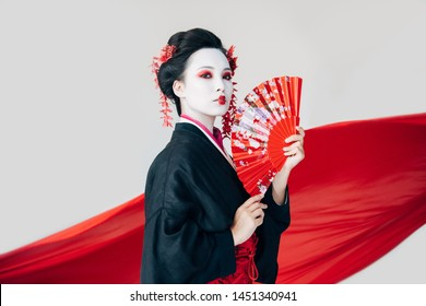 beautiful geisha in black kimono with hand fan and red cloth on background isolated on white