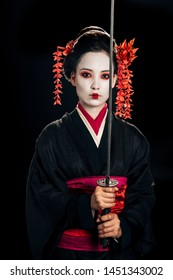 beautiful geisha in black kimono with red flowers in hair holding traditional katana isolated on black