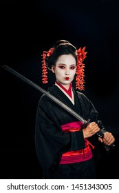 beautiful geisha in black kimono with red flowers in hair holding katana isolated on black