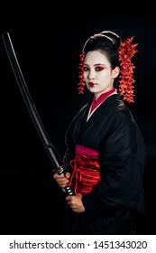beautiful geisha in black kimono with red flowers in hair holding sharp katana isolated on black