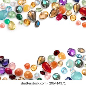 Beautiful gems composition with empty space in the middle. Bright real gems: labradorite, ruby, amethyst, blue topaz, citrine, rose quartz, garnet, moonstone rainbow, prehnite... on white background.