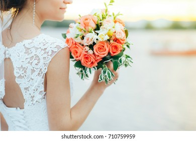 beautiful and gentle bride is holding a wedding bouquet in her hands, against the background of the sea and sunset.