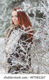 beautiful gentle girl with red hair in a fur vest standing in a snowy forest with iniem on the branches of trees
