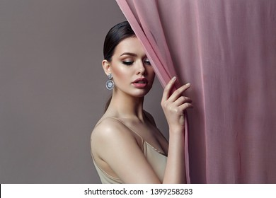 A beautiful, gentle, romantic girl is standing behind a transparent curtain in elegant diamond earrings.