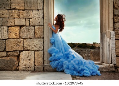 Beautiful, gentle, young woman in nature. In a blue dress, stands near the ancient ruins, against a cloudy sky.