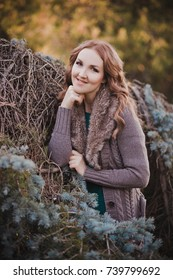 Beautiful genuine lady mystic with curly brunette hairs and adorable eyes dressed in fancy stylish warm clothes with fur on neck lonely posing sit for camera in autumn dark forest.