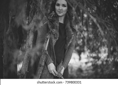 Beautiful genuine lady mystic with curly brunette hairs and adorable eyes dressed in fancy stylish warm clothes with fur on neck lonely posing sit for camera in autumn dark forest black and white