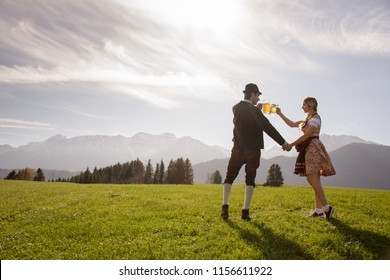 Beautiful german young couple in traditional clothes cheering beer mugs. Oktoberfest