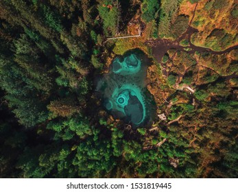 Beautiful Geyser (blue, silver) lake with thermal springs that periodically throw blue clay and silt from the ground. Aerial drone view. Aktash, Altai mountains, Russia