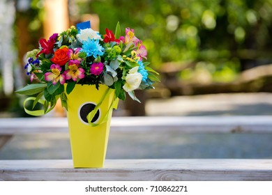 Beautiful gift bouquet in a yellow vase on a wooden bench. Wedding decorations.