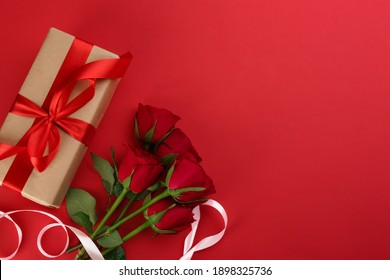 Beautiful gift box and roses on red background, flat lay with space for text. Valentine's day celebration