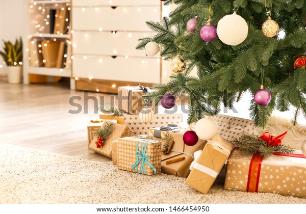 Beautiful gift boxes under fir tree in room