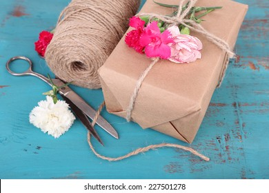 Beautiful gift with flowers and decorative rope, on old wooden background