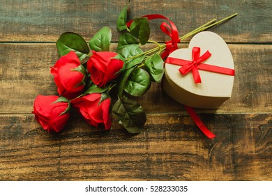 Beautiful gift with heart shape with a bouquet of red roses on a wood background