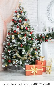 Beautiful gift lies near the decorated Christmas tree