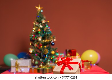 Beautiful gifts box with red ribbon on table at Christmas tree and lights background.Christmas concept,selective focus