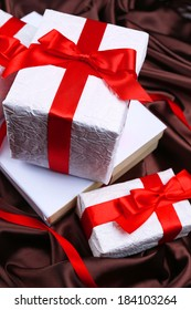 Beautiful gifts with red ribbons on silk background