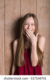 Beautiful giggling teen girl in red top against a concrete background