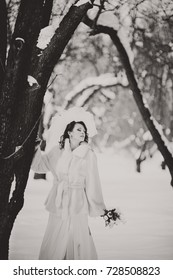 The beautiful ginger bride in a white fur coat with a bouquet of white flowers in a park. Winter wedding outdoors. Black and white photography.