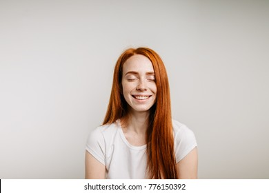 Beautiful ginger girl smiling posing with closed eyes.