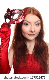 Beautiful ginger young girl in red dress with masquerade mask and red gloves