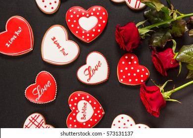 Beautiful gingerbread heart and red roses on a black background. Postcard for Valentine's day, March 8, mother's day or Wedding