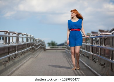 Beautiful ginger-haired woman in blue dress and red belt walking on the bridge at summer