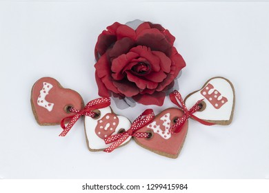 Beautiful gingersnap in the form of four hearts connected by ribbons and an inscription love and a big red rose close up on a white background