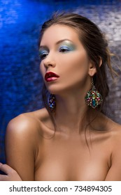 The beautiful gir wearing a wearing a earrings on a colourful foil background. Stylized as evening light. Evening colourfull make-up. Red lips. Clean healthy skin.