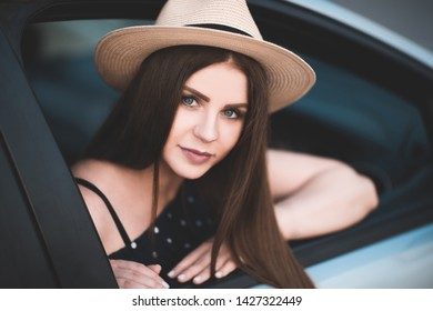 Beautiful girl 20-24 year old wearing straw hat sitting in car. Looking at camera. Summer time.