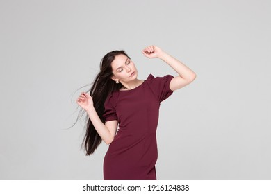 a beautiful girl of 25 years old, European appearance, with dark long hair, in a burgundy dress, stands on a light gray background in the studio, in full growth. Portrait of a girl, brunette,