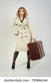 A beautiful girl from 50-60's in retro style in a raincoat and with a suitcase.