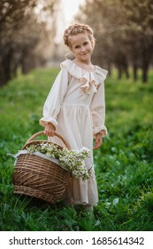 Beautiful girl 6-7 year old posing in garden in white dress. Easter time. enjoys spring and warmth. Happy childhood, peace and happiness concept. Aromatic blossom and retro vintage.