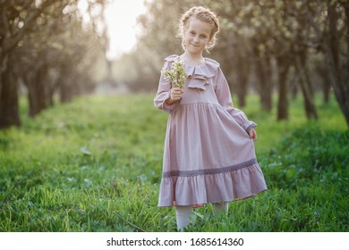 Beautiful girl 6-7 year old posing in garden. Easter time. enjoys spring and warmth. Beautiful spring garden. Happy childhood, peace and happiness concept. Aromatic blossom and retro vintage.