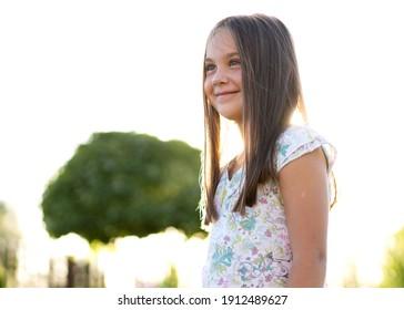 schönes Mädchen von 8 Jahren, das sich bei Sonnenuntergang auf einem Garten in der Nähe ihres Hauses