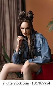 Beautiful girl with an afro cornrows hairstyle, wearing a casual denim jacket, is resting on a chair standing on an old carpet near to a palm tree in a pot. Fashionable, commercial, modern design