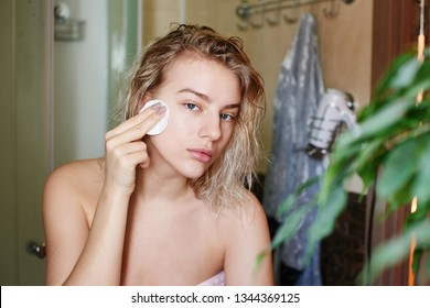 A beautiful girl after shower looks into the camera as in mirror and cleans her face from make up with a cotton pad in the bathroom