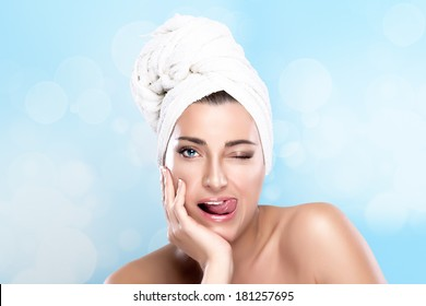Beautiful girl after shower winking with towel on head and funny expression sticking his tongue. Spa treatment. Haircare concept. Gestures and grimaces