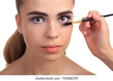 A beautiful girl aligning her eyelashes with mascara on a white isolated background