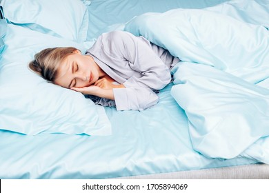 Beautiful girl alone sleeps in bed. A young woman lies on blue silk bedding on a hotel bed. Blue bedding made of natural silk.